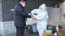 Un hombre se somete a un control de temperatura antes de entrar en un colegio electoral durante las elecciones generales de Corea del Sur.