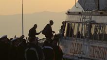 Refugiados son escoltados a un ferri en el puerto de Mytilene en la isla de Lesbos en Grecia este lunes