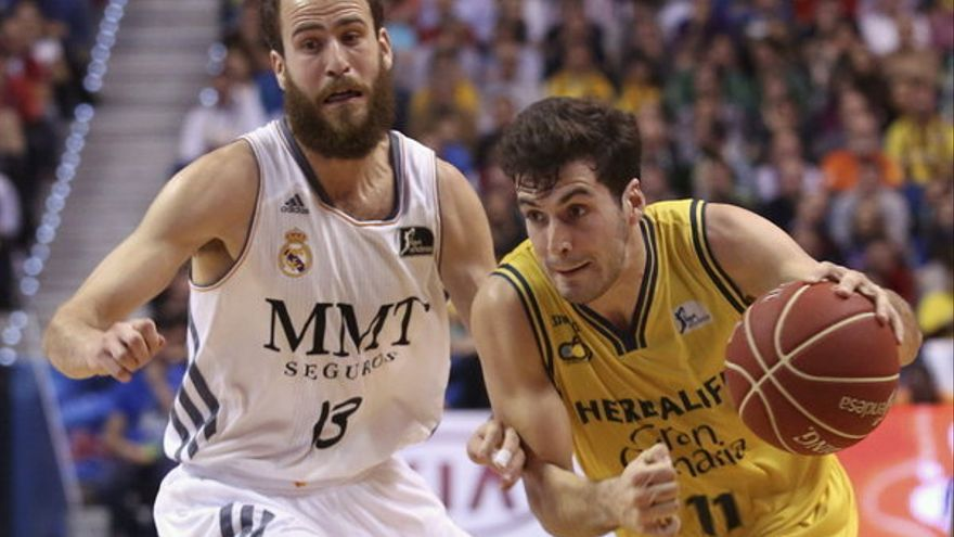 El base del Herbalife Gran Canaria Tomás Bellas (d) entra a canasta ante la defensa del base del Real Madrid Sergio Rodriguez. (Carlos Díaz/Efe).