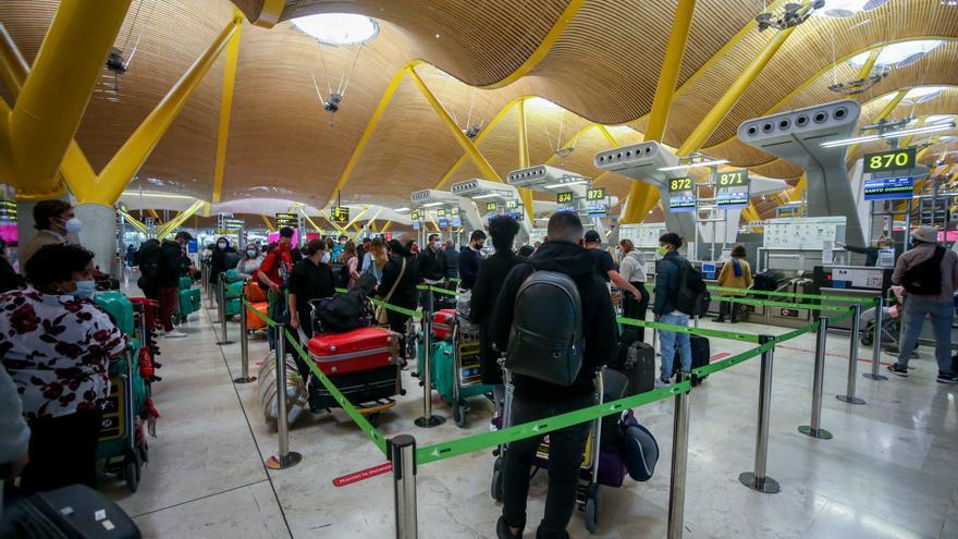 Filas de pasajeros esperan para dejar su maleta antes de embarcar en el avión en la T4 del Aeropuerto Adolfo Suárez Madrid-Barajas, en Madrid, (España).
