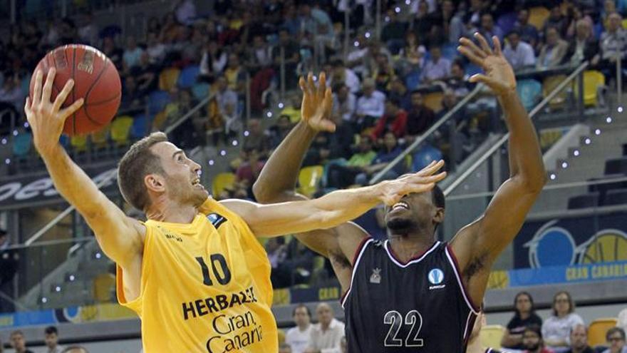El jugador del Herbalife Gran Canaria Txemi Urtasun lanza a canasta ante el jugador del Arland Dragons Quakenbrueck Antonio Graves. EFE/Elvira Urquijo A.