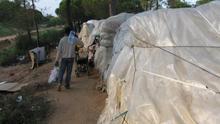 Un inmigrante transporta agua para beber y cocinar en un asentamiento en Lepe.