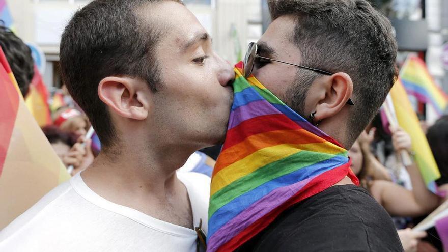 Dos hombres besándose en una marcha del Orgullo