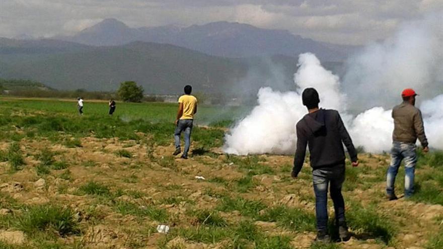 Un grupo de refugiados se aleja del gas lanzado por la policía de Macedonia en la frontera de Idomeni, en territorio griego.