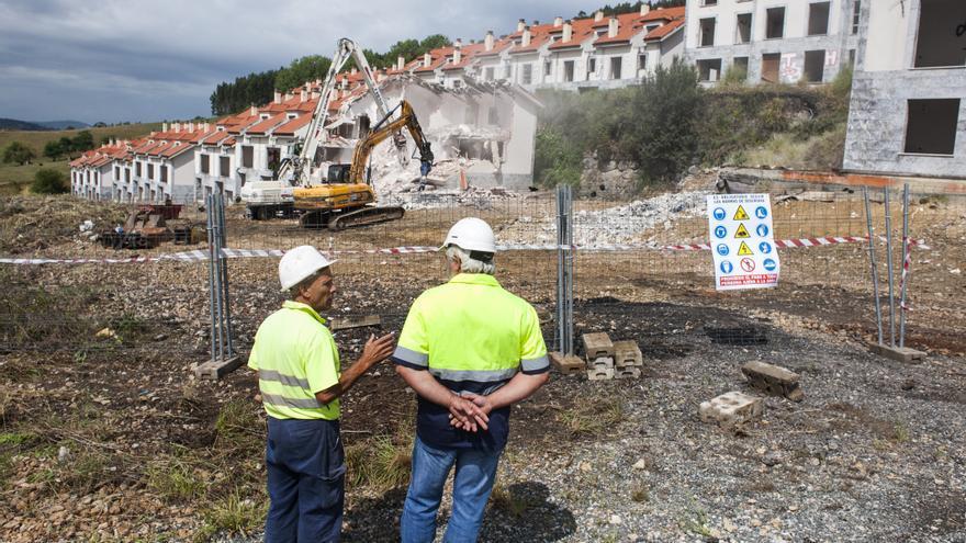 Dos operarios observan cómo las palas derriban las viviendas. | JOAQUÍN GÓMEZ SASTRE