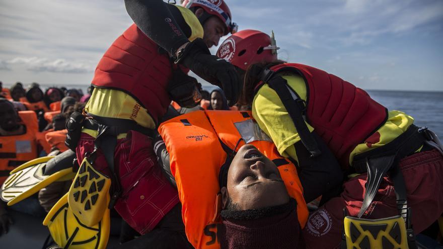 Los socorristas de Proactiva Open Arms suben a su embarzación a una de las mujeres rescatadas.