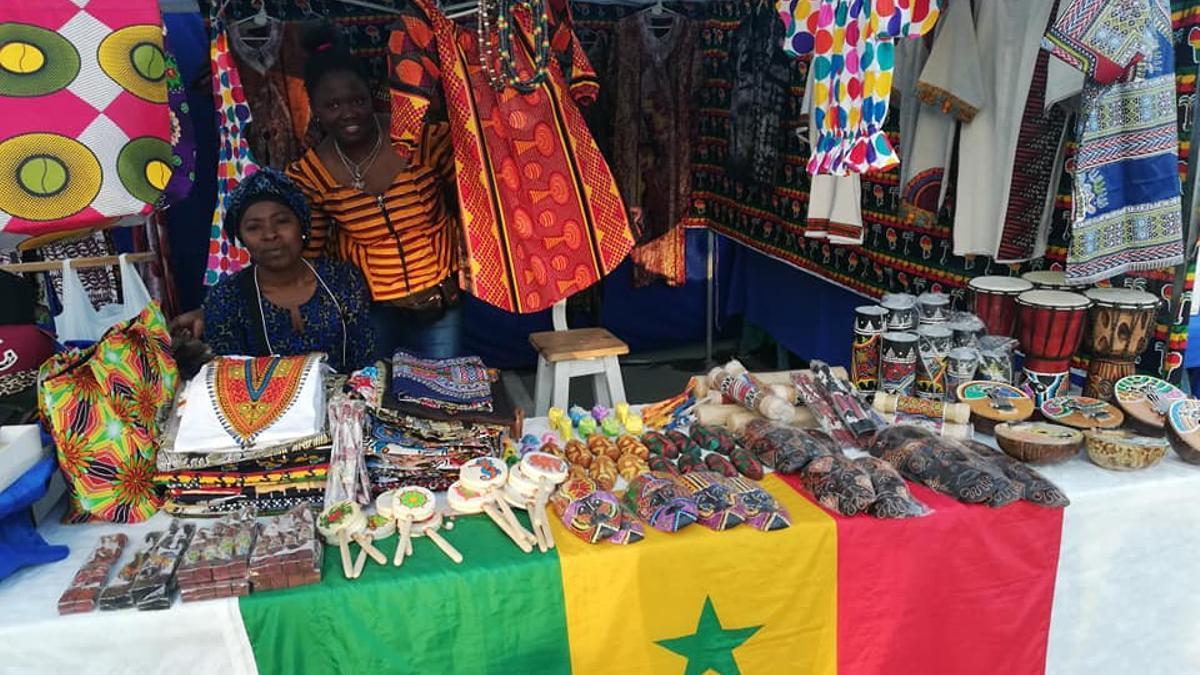 Seyna con su emprendimiento de ropa senegalesa participando de una feria