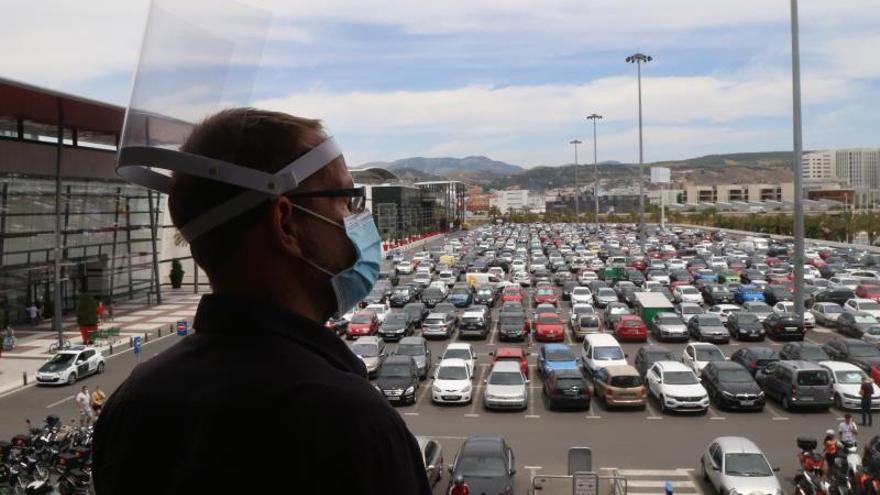 Un hombre observa los aparcamientos del Centro Comercial Nevada, en Armilla, Granada, que ha abierto sus puertas hoy lunes cuando esta provincia ha pasado a la fase 2 de la desescalada en el estado de alarma por la crisis sanitaria de la COVID-19.