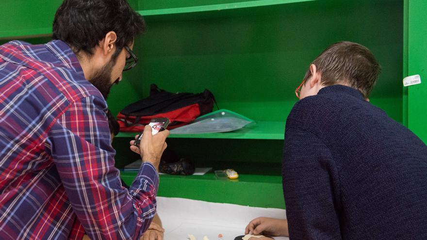 Un profesor del Instituto Barres i Ones de Badalona consulta el móvil con uno de sus alumnos