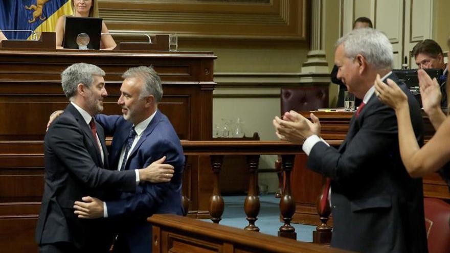 El presidente de Canarias, Ángel Víctor Torres (c), es felicitado por el ex presidente Fernando Clavijo, tras finalizar el debate del pleno de investidura.