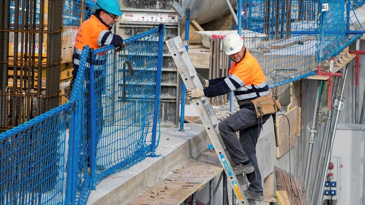 Varios obreros trabajan en la obra de un edificio de viviendas de nueva construcción.