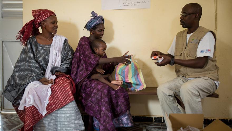 Pape Sall, agente psicosocial de Acción contra el Hambre, entrega a Aminata el alimento terapéutico Pumply Nut.
