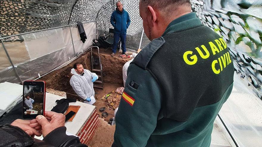 Un agente de la Guardia Civil, junto a la fosa común de Pinos Genil (Granada).  