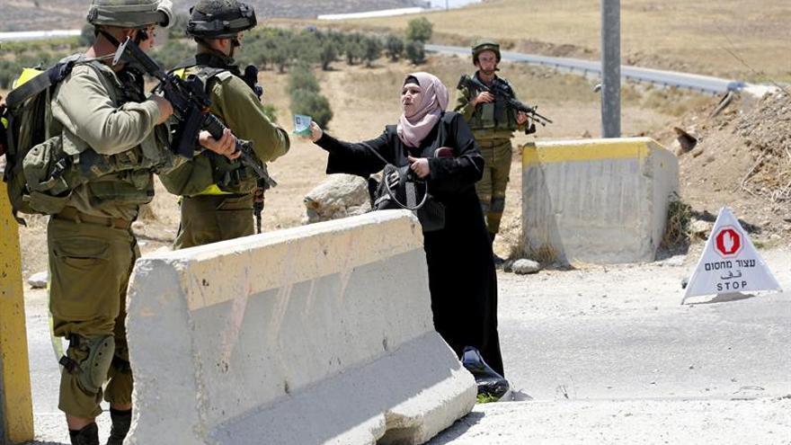 Una mujer palestina discute con los soldados israelíes en un punto de control.