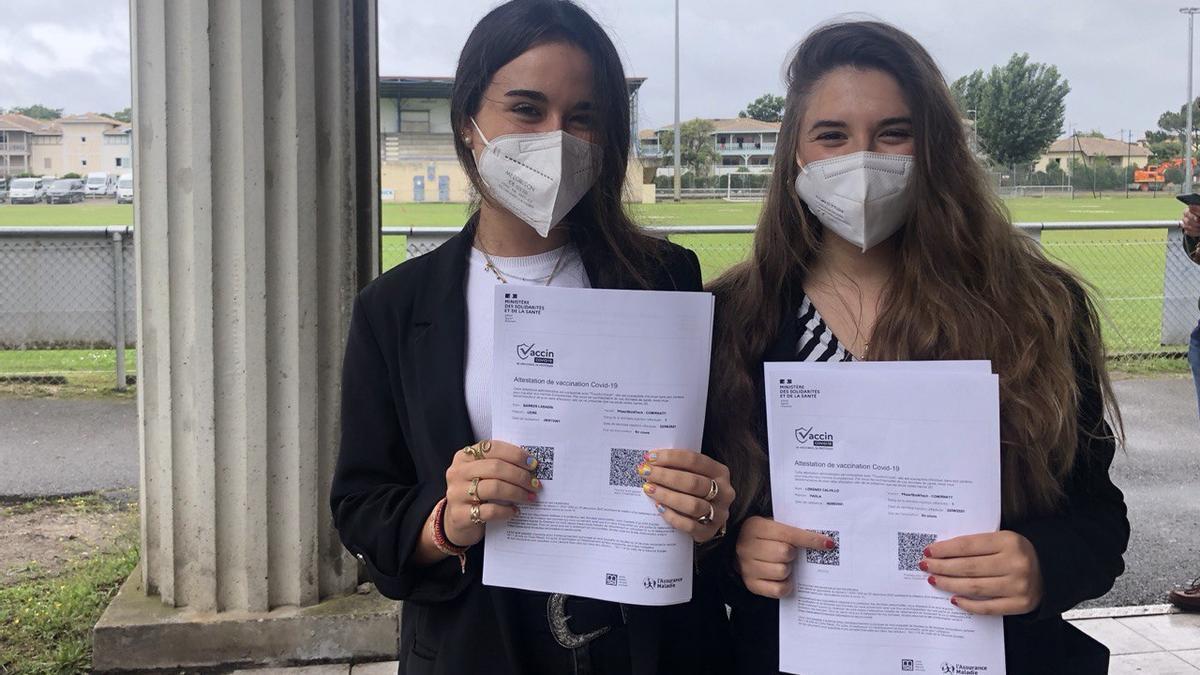 Leire Barros y Paola Lorenzo con el certificado que acredita que han recibido la primera dosis de la vacuna contra la COVID-19