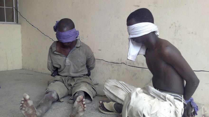 Dos sospechosos de pertenecer al grupo islamista Boko Haram, detenidos por militares en Bukavu Barracks, en el estado de Kano, Nigeria. © AP Photos/Salisu Rabiu-file