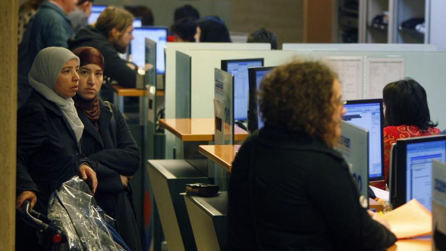 Mujeres migrantes aguardan en una cola en una oficina de Lanbide (Servicio Vasco de Empleo).