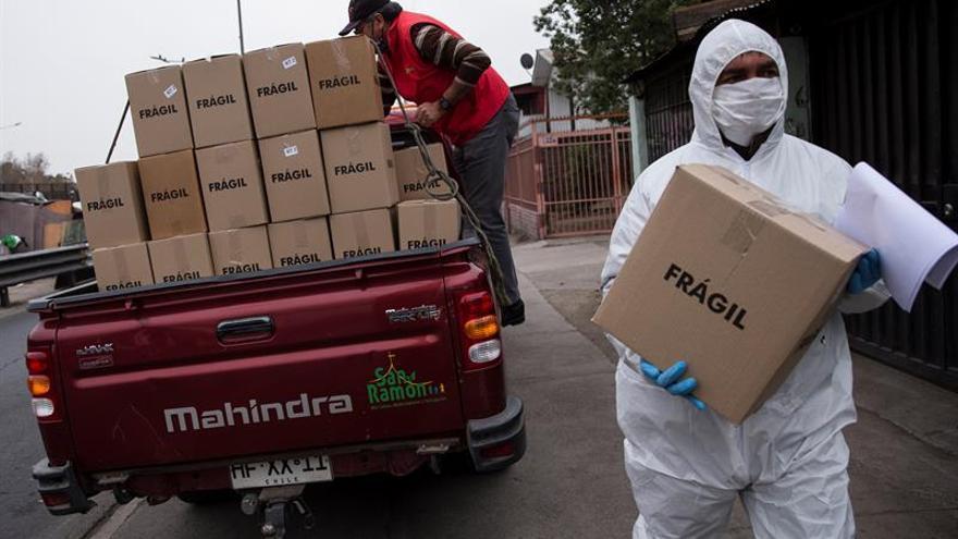 Trabajadores municipales de la comuna de San Ramón reparten cajas con alimentos básicos a familias vulnerables afectadas por las consecuencias de la cuarentena obligatoria decretada para detener el avance de la COVID-19, este jueves, en Santiago (Chile).