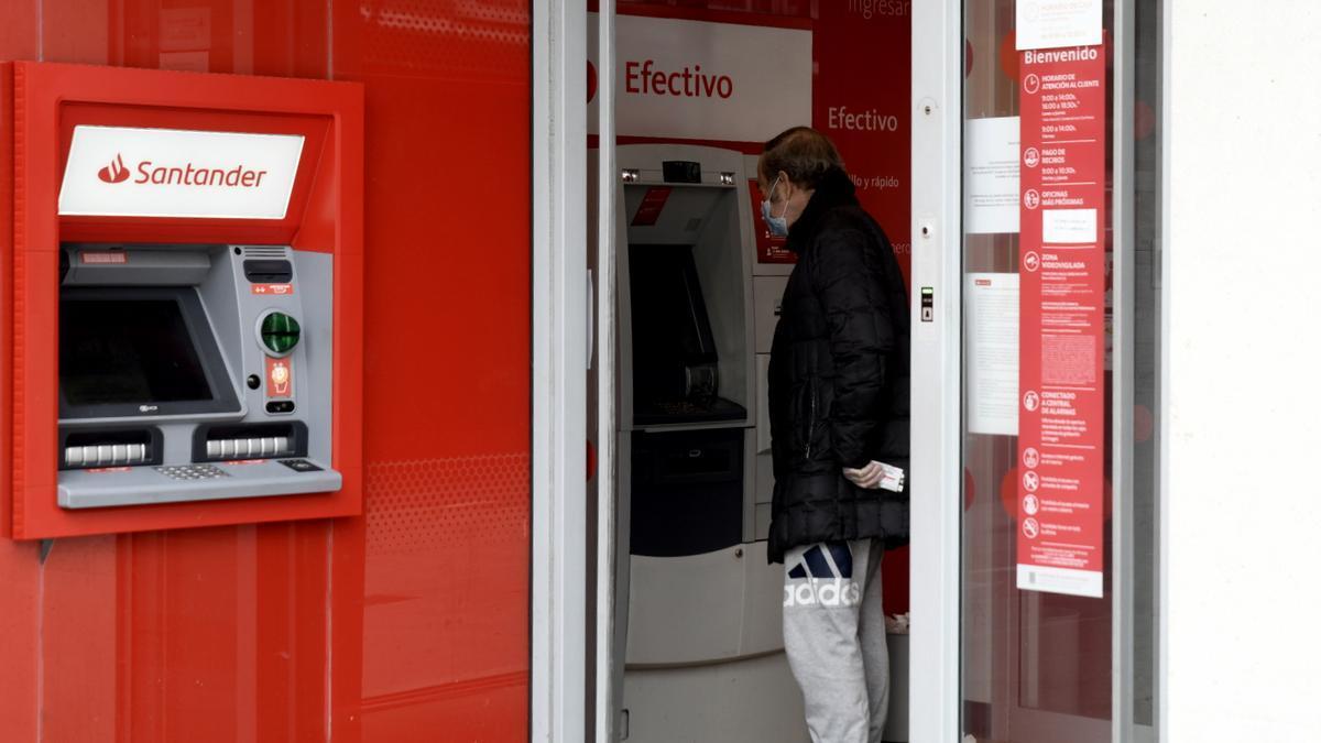 Un hombre saca dinero de un cajero del Banco Santander.