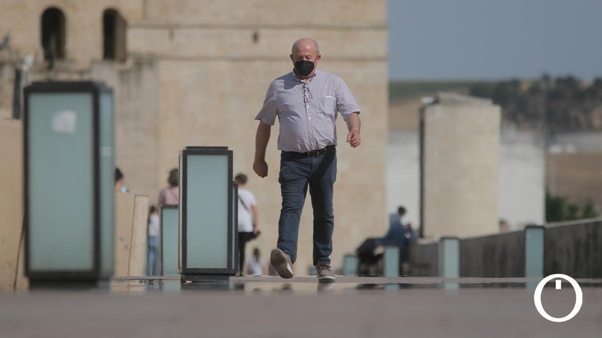 Un hombre pasea por el Puente Romano a pleno sol