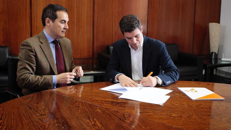 Los portavoces de PP y Ciudadanos en el Parlamento, José Antonio Nieto y Sergio Romero, firman el acuerdo para reformar el Estatuto.