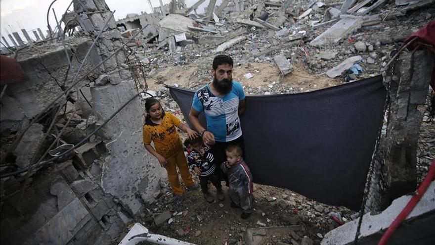 El palestino Madi Kamil Hassanin y su familia permanecen junto a su casa destrozada, en el barrio Al-Sha-af del este de Gaza. / Efe