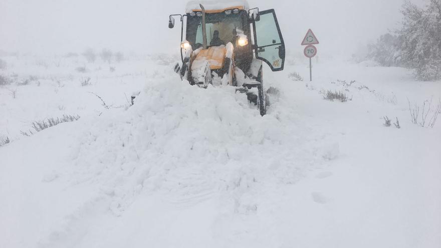 Una retroexcavadora trabaja para desalojar nieve de la carretera