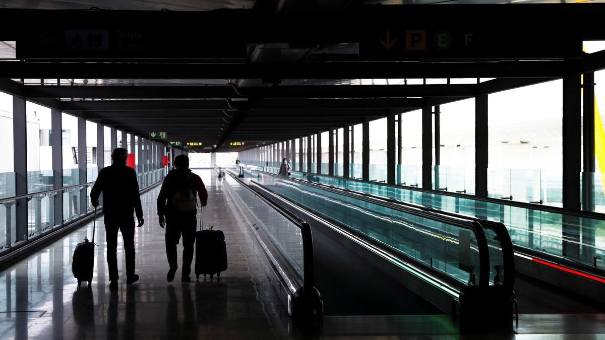 Dos pasajeros cruzan una de las terminales del Aeropuerto Adolfo Suárez Madrid-Barajas