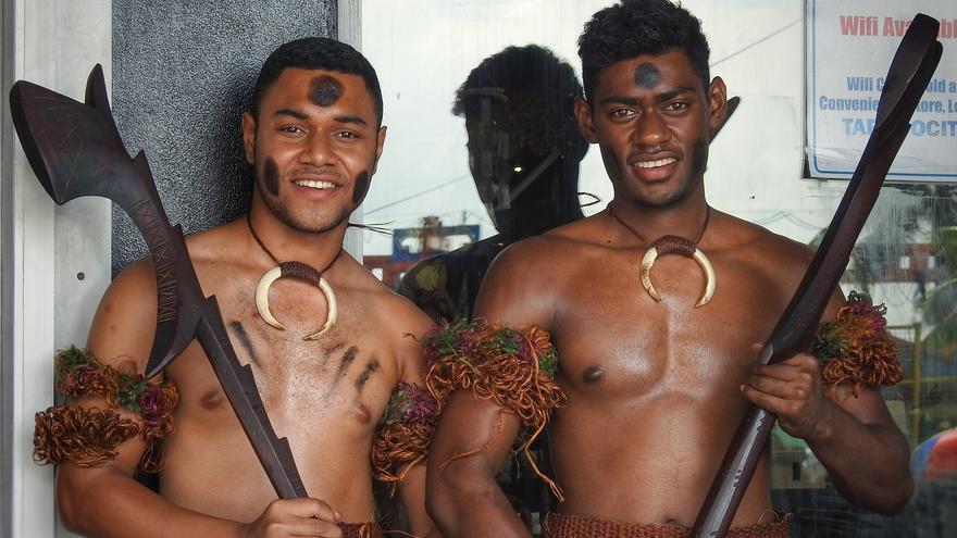 Dos fiyianos lucen la 'vestimenta' y antiguas armas tradicionales. Dennis Sylvester Hurd