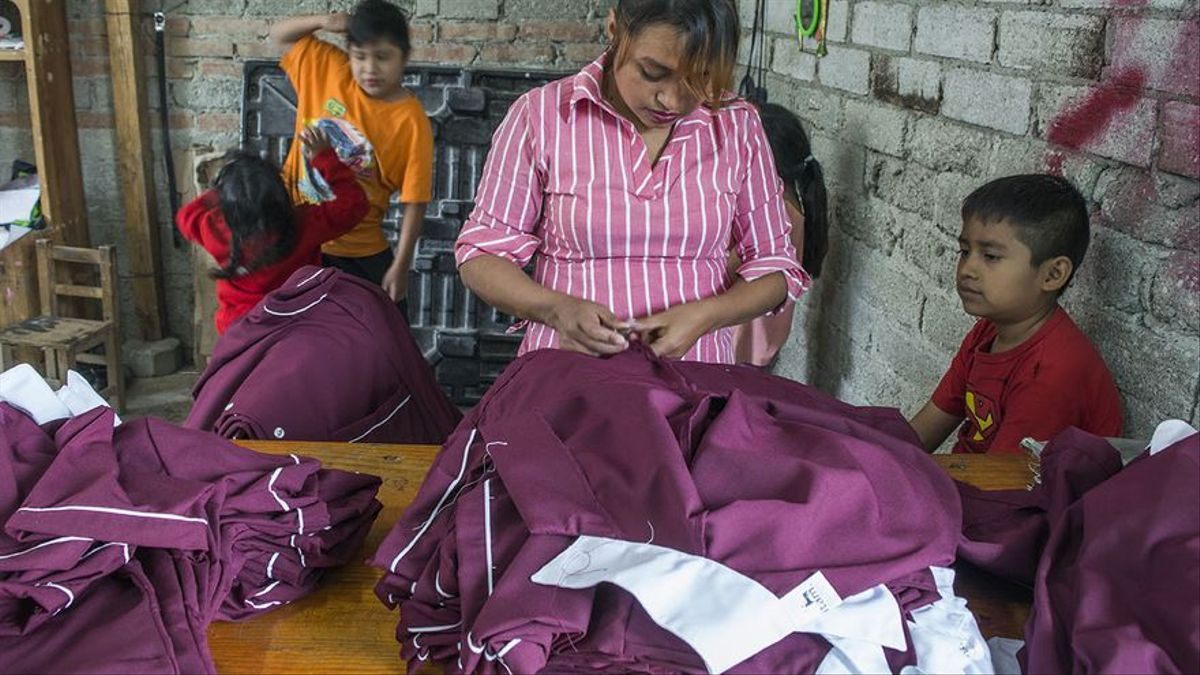 Una mujer trabaja en un taller familiar rodeada de sus hijos ya que no van a la escuela por la suspensión de clases por la emergencia de la Covid-19.