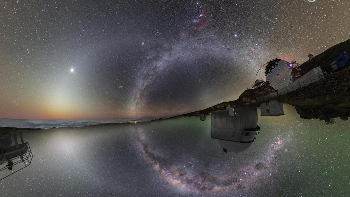 En la parte superior de la imagen, el Observatorio del Roque de Los Muchachos (Garafía, La Palma), tomada en febrero de 2020. La zona inferior refleja el cielo del hemisferio sur desde el Observatorio La Silla (ESO Astronomy), en abril de 2016. En esta composición, la Vía Láctea corre casi verticalmente por encima y por debajo del horizonte. En la mitad superior, Venus está inmerso en la luz zodiacal, que crea un círculo completo a través del cielo estrellado. También se pueden ver Andrómeda y las Nubes de Magallanes. Las cúpulas de los telescopios del observatorio de La Silla, aparecen boca abajo. Esta imagen, firmada por los astrofotógrafos Juan Carlos Casado y Petr Horálek fue Astronomy Picture of the Day (APOD) el 27 de febrero de 2020 (apod.nasa.gov/apod/ap200227.html).
