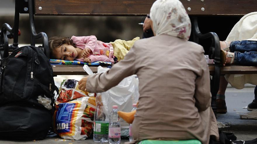 Una madre y su hija descansan dentro de la estación de tren de Budapest