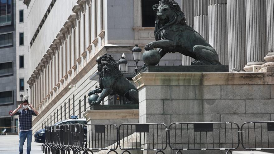 Un hombre se coloca una mascarilla mientras camina por delante de la fachada del Congreso