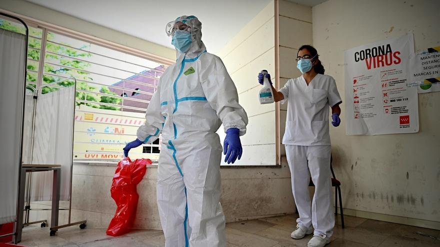 Dos trabajadores proceden a desinfectar sus trajes.