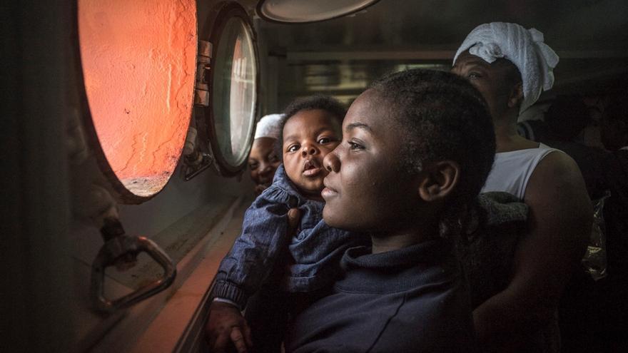 Una mujer y su bebé miran por la ventana antes de atracar a tierra. En 2016, más de 180.000 personas llegaron a Italia tras jugarse la vida en el Mediterráneo central. Una de cada 9 fueron rescatadas por los equipos de MSF en del Dignity I, el Bourbon Argos y el Aquarius. No obstante, más de 4.600 personas han fallecido en el intento en esta ruta mortal. © yann Merlin/SOS MEDITERRANEE