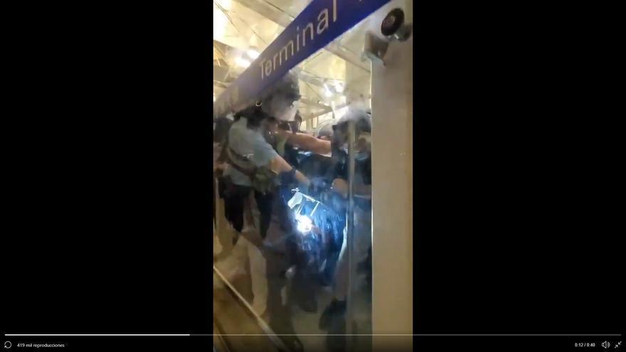Captura de un vídeo en el que varios manifestantes quitan la porra a un agente antidisturbios.
