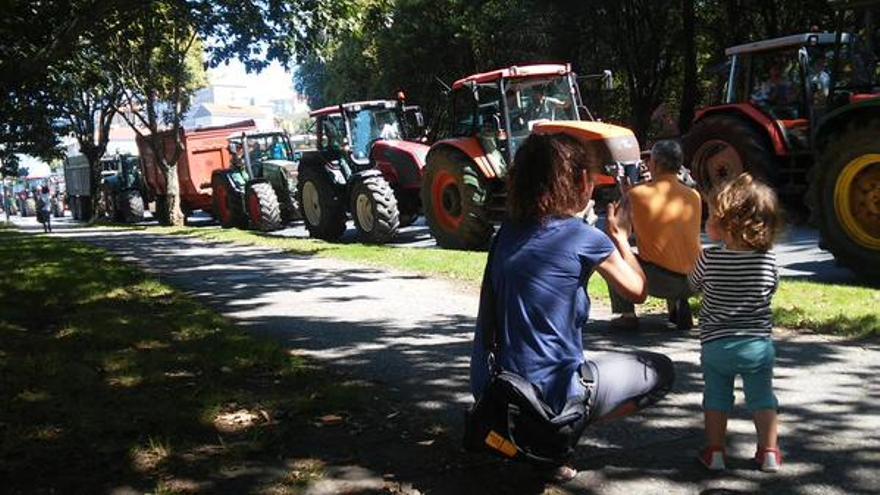 Una mujer y su hija aplauden al paso de los tractores / Merixo