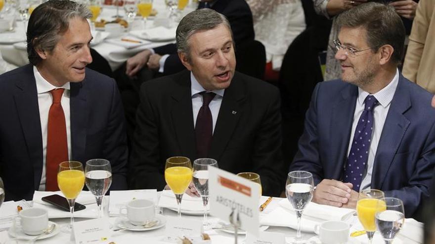 El ministro de Fomento, Íñigo de la Serna (i), conversa con el ministro de Justicia, Rafael Catalá (d), en presencia del presidente de EY España, José Luis Perelli
