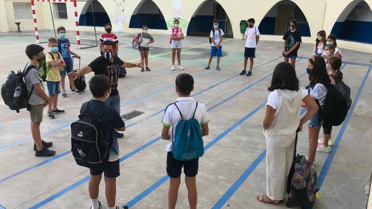 Alumnos con mascarillas y la distancia de seguridad en el patio de un centro docente