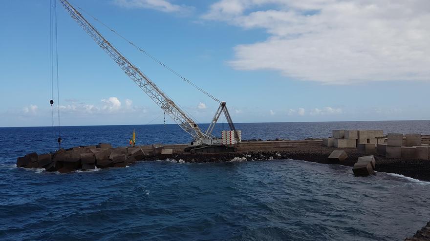 Un grúa de grandes dimensiones participa en los trabajos de reparación de la escollera. Foto: LUZ RODRÍGUEZ.