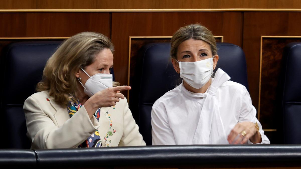 La ministra de Economía, Nadia Calviño (i) conversa con la ministra de Trabajo, Yolanda Díaz (d) durante una sesión en el Congreso.