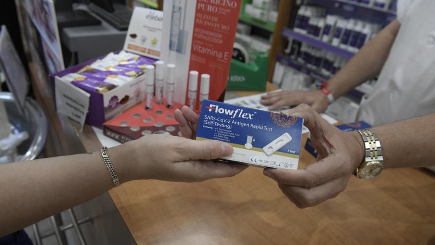 Un farmacéutico enseña un test de antígenos de detección del COVID-19 en una farmacia.