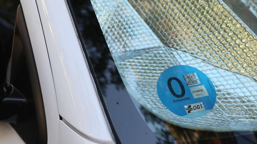 Una etiqueta ambiental de la DGT, colocada en el parabrisas de un coche