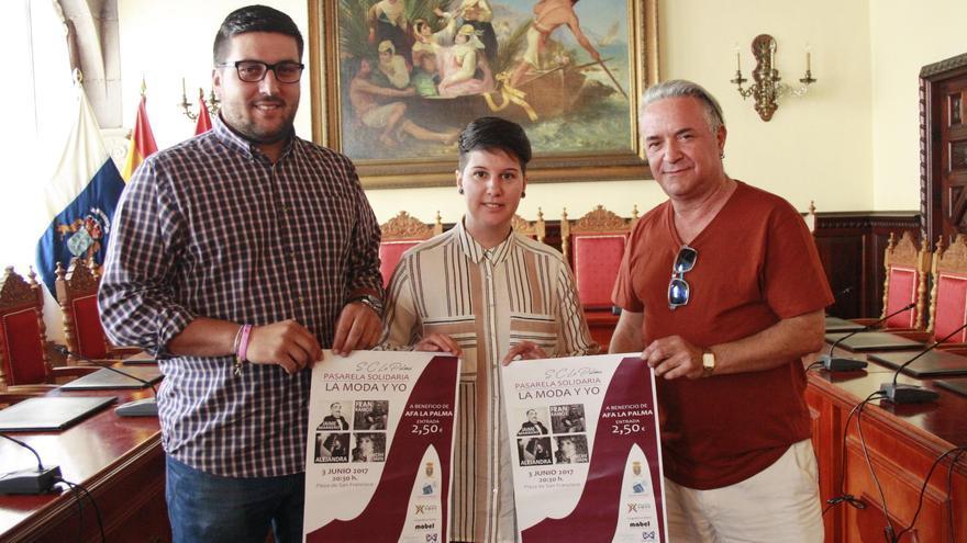Los organizadores de la gala solidaria 'La moda y yo'  muestran el cartel.