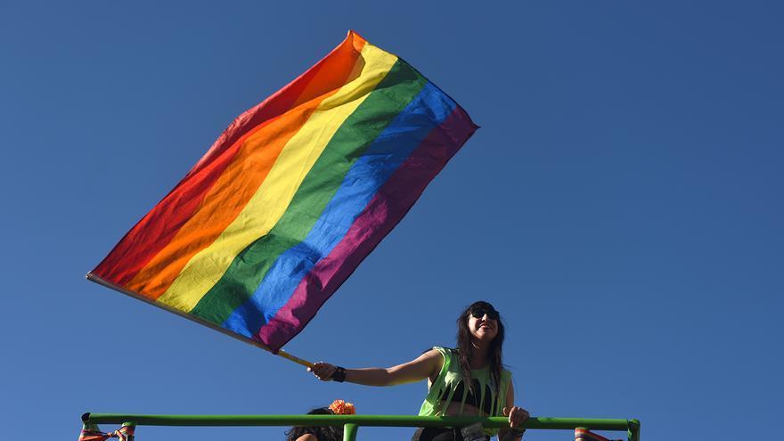 Una manifestante ondea la bandera LGTBI en una carroza.