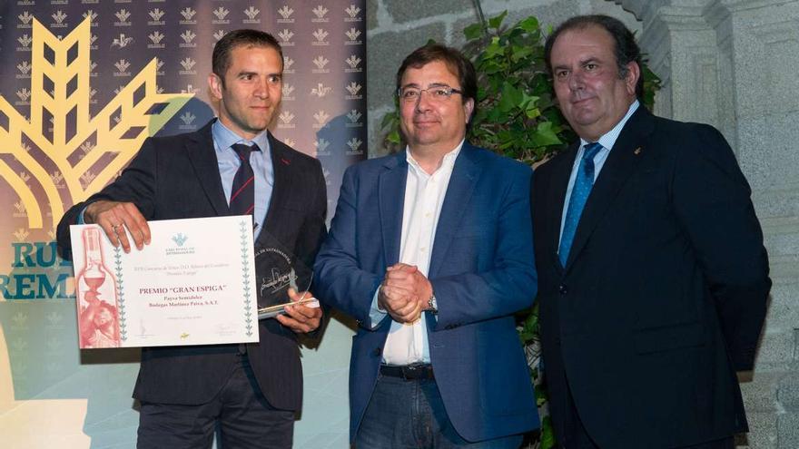 El presidente de la Junta con el de la Caja (derecha) y uno de los premiados