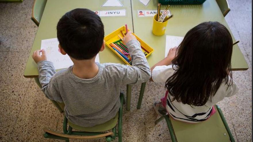 Un niño y una niña sentados en un aula. Foto de archivo.