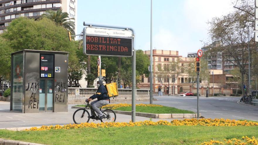 Un trabajador de reparto a domicilio conduce su bici en Barcelona el domingo pasado
