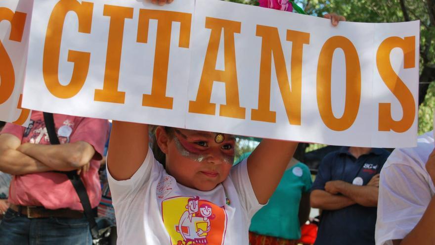 Una joven gitana sostiene un cartel en una Jornada de Puertas Abiertas organizada por la Fundación Secretariado Gitano