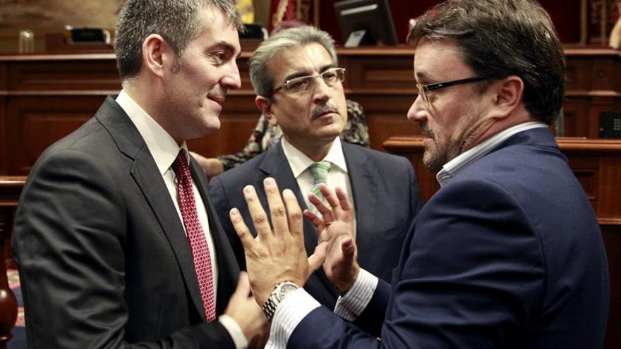 El presidente del Gobierno de Canarias, Fernando Clavijo (i), conversa con los diputados de Nueva Canaria, Román Rodríguez (c), y del Partido Popular, Asier Antona, antes de comenzar la sesión plenaria del Parlamento regional. (EFE/Cristóbal García).
